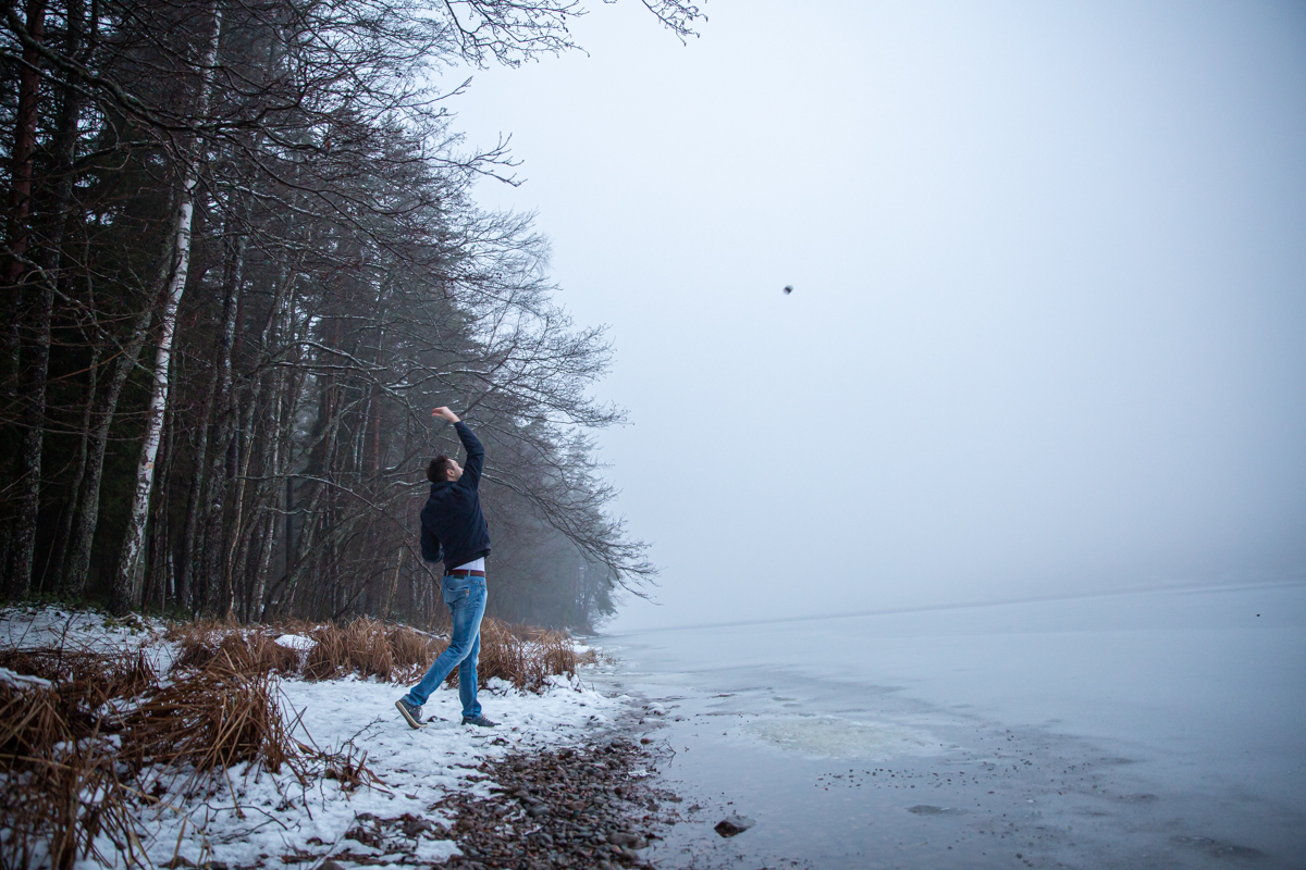 Photographer's brother throwing a rock on the ice of lake Saimaa.