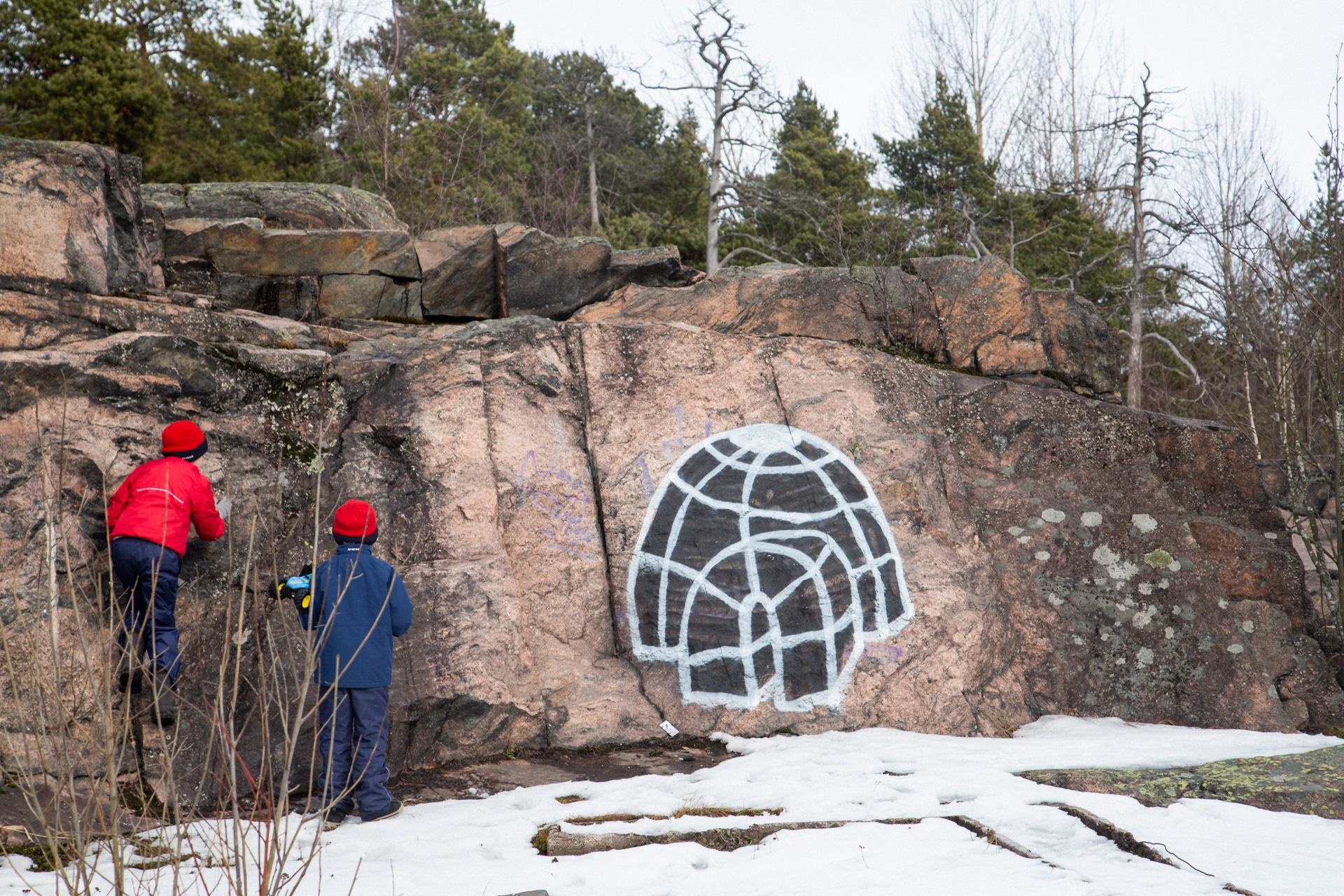 Children by the rock with a graffiti depicting an iglu.