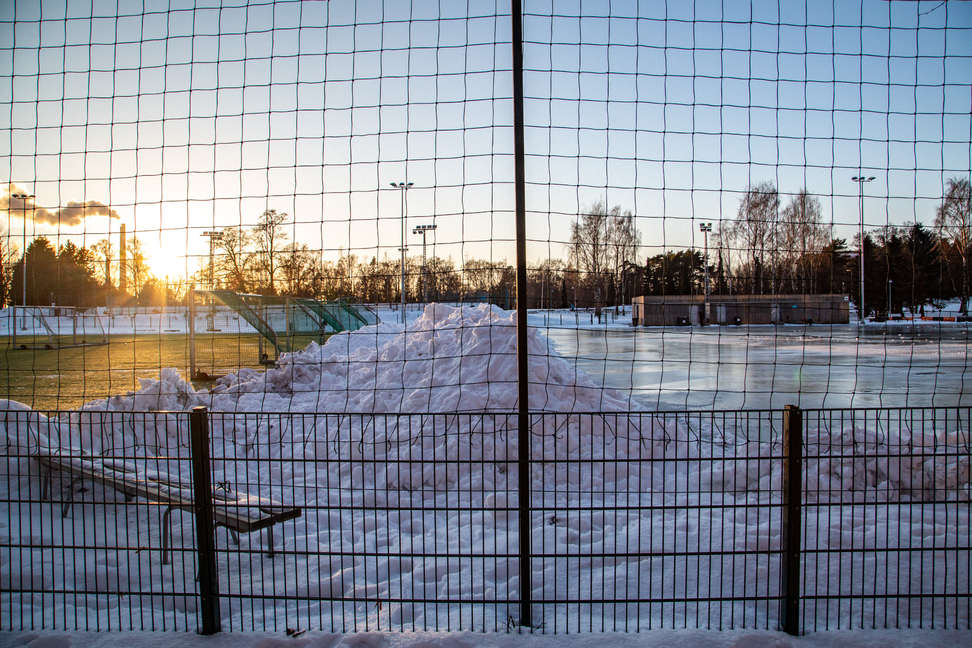 A view over a sports field that has a soccer field on the left and an ice skating area on the right.