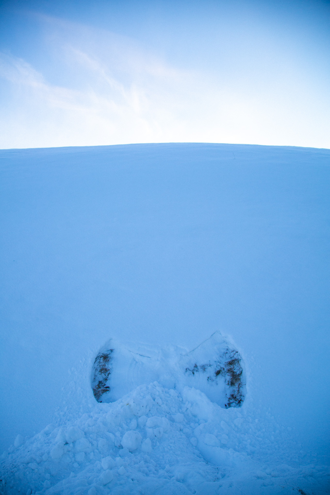 Snow angel by a hill with snow ploughed on it.