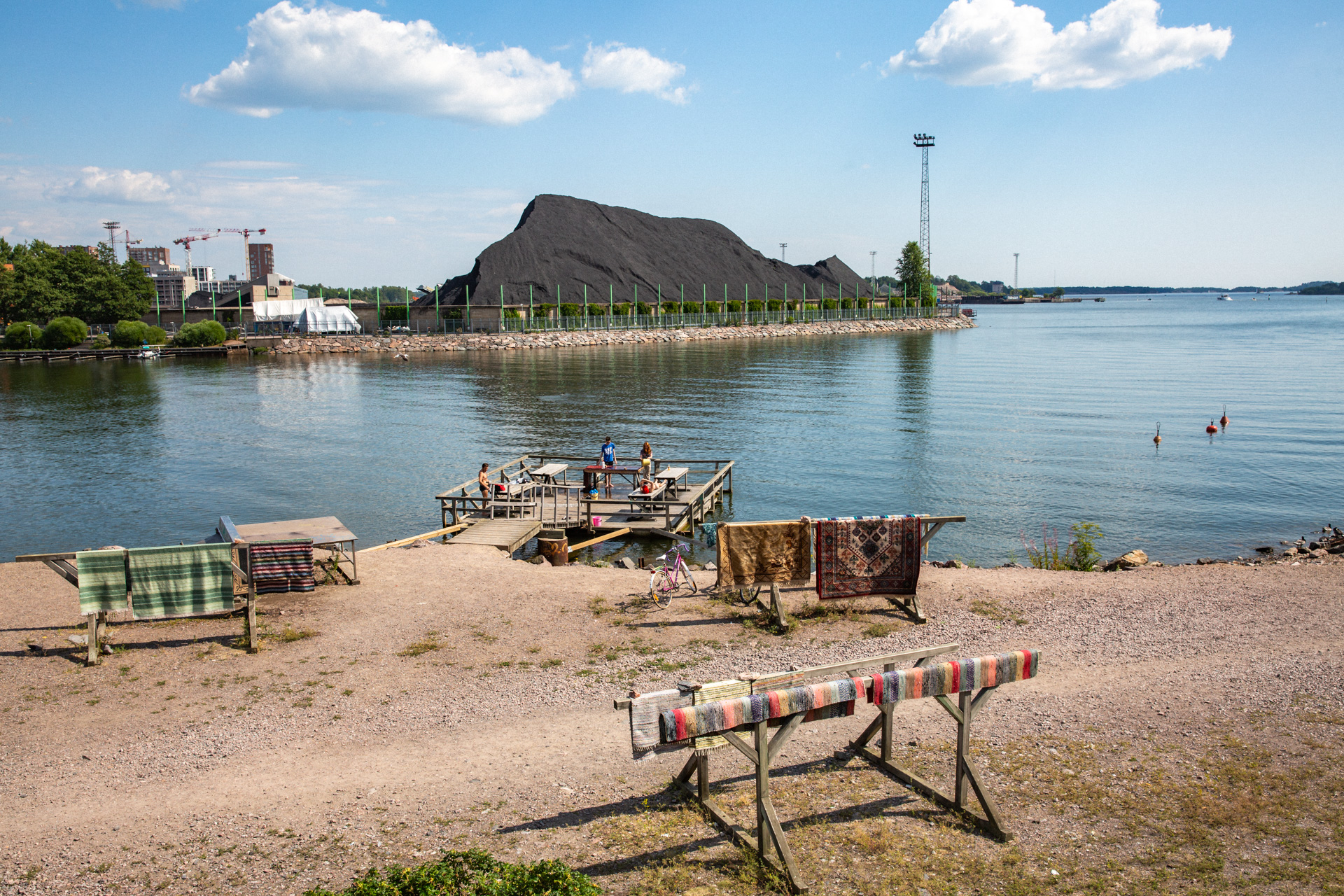 People sunbathing and washing carpets in front of a pile of coal in Helsinki.