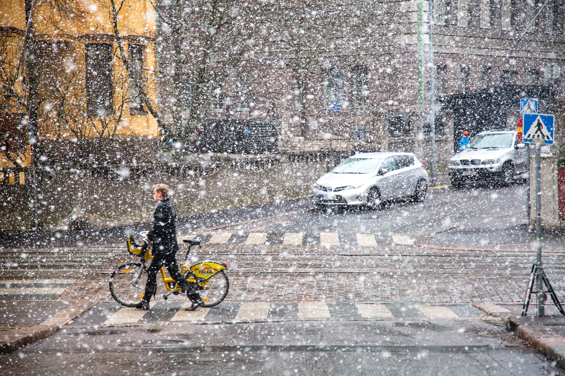 A heavy snowfall in May and a man crossing the street with an Alepa city bike.