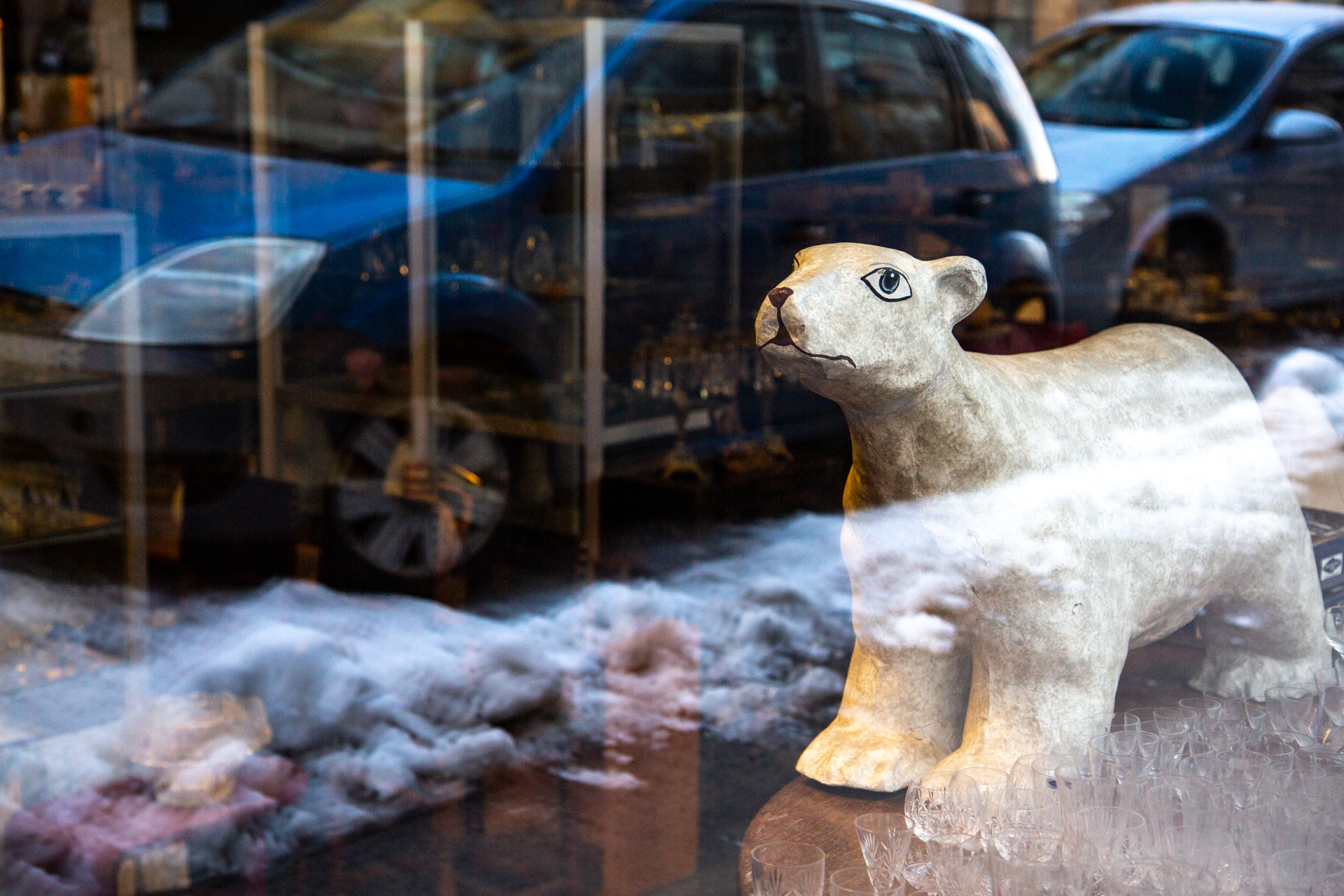 An antique polar bear in the window with reflections of snow and cars parked by the street.